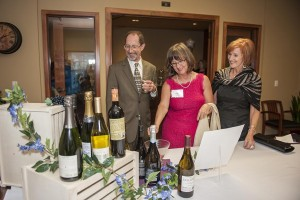 """Stephen Young, Kathy Kremer, and Kathleen Dailey, check out the """"Wines of the World"""" raffle prize."""